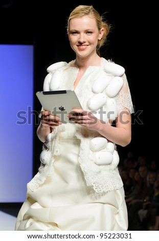 BARCELONA – MAY 19: A model walks on the Fran Baviera catwalk with an ipad during the Barcelona Bridal Week runway on May 11, 2011 in Barcelona, Spain. - stock photo