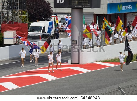 """BARCELONA - MAY 9: Girls leave with flags in honor of participants, autodrome """"Catalunya Montmello"""" before beginning The Formula 1 Grand Prix on may 9, 2010 in Barcelona, Spain"""