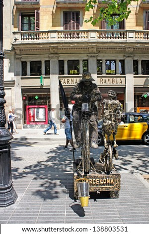 BARCELONA - MAY 29: Street Performer imitating bronze statue on a bicycle with a skeleton, famous La Rambla street, Barcelona, Catalunia, Spain on 29 May 2012.