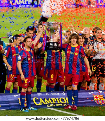 BARCELONA - MAY 15: Xavi Hernandez and Carles Puyol holds the Spanish League Championship Trophy in Camp Nou stadium, on May 15, 2011 in Barcelona, Spain.