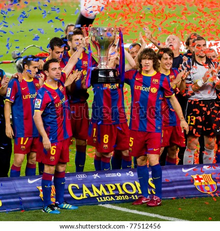 BARCELONA - MAY 15: Xavi Hernandez (L) and Carles Puyol hold the Spanish League Championship Trophy in Camp Nou stadium, on May 15, 2011 in Barcelona, Spain.