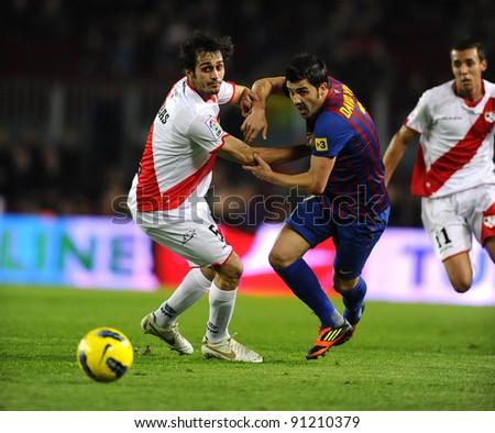 BARCELONA - NOV 29: Alejandro Arribas of Rayo Vallecano vie with David Villa of FC Barcelona during the spanish league match at the Nou Camp Stadium on November 29, 2011 in Barcelona, Spain