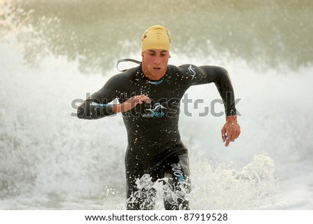 BARCELONA - OCT, 16: Cristian Cofine of Spain in action finishing swimming at Barcelona Garmin Triathlon event at Barcelona beach on October 16, 2011 in Barcelona, Spain - stock photo