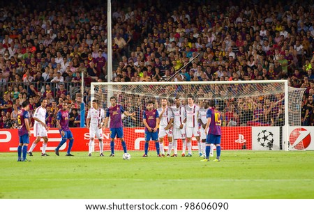 BARCELONA - SEPTEMBER 13: Leo Messi (10) shoots a free kick during the Champions League match between FC Barcelona and Milan, final score 2 - 2, on September 13, 2011, in Camp Nou, Barcelona, Spain.