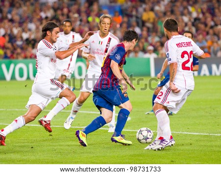 BARCELONA - SEPTEMBER 13: Lionel Messi (middle) in dribbling action during the Champions League match between FC Barcelona and Milan, final score 2 - 2, on September 13, 2011, in Barcelona, Spain. - stock photo