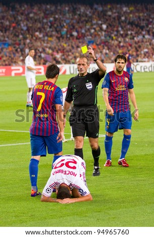 BARCELONA - SEPTEMBER 13: Referee giving yellow card to David Villa during the UEFA Champions League match between FC Barcelona and AC Milan, 2 - 2, on September 13, 2011, in Barcelona, Spain.