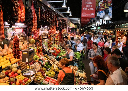BARCELONA - SEPTEMBER 9: Tourists in famous La Boqueria market on September 9, 2009 in Barcelona. One of the oldest markets in Europe that still exist. Established 1217.