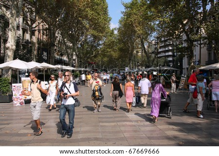 BARCELONA - SEPTEMBER 13: Tourists strolling famous Ramblas on September 13, 2009 in Barcelona. Rambla boulevard is one of the most recognized streets in the world.