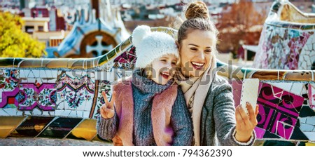 Barcelona signature style. Portrait of smiling trendy mother and daughter tourists in Barcelona, Spain with smartphone taking selfie while sitting on a bench #794362390