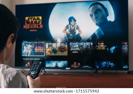 Barcelona, Spain. April 2020: Back view image of cute little boy watching Star Wars revbels tv series .Illustrative editorial