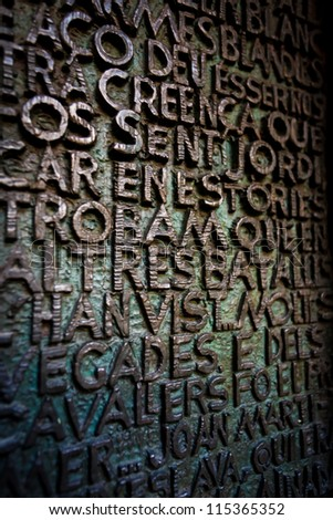 BARCELONA, SPAIN - APRIL 21, 2010 Pattern of bronze raised letters covered with green patina on wall plaque in Sagrada Familia the # 1 tourist spot in Barcelona on April 21, 2010 in Barcelona, Spain.