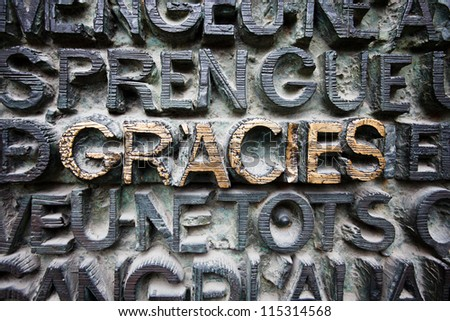 BARCELONA, SPAIN - APRIL 22, 2010: Pattern of raised letters covered with patina, GRACIES gold highlighted in center on April 22, 2010 in the #1 tourist attraction, Sagrada Familia, Barcelona, Spain.