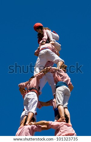 "BARCELONA, SPAIN - APRIL 29: The Castellers group ""Xiquets de Tarragona"" performing a traditional catalan human pyramid on April 29, 2012 in Barcelona, Spain."
