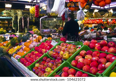 BARCELONA, SPAIN - APRIL 27: Tourists shop in famous La Boqueria market on April 27, 2012 in Barcelona, Spain.One of the oldest markets in Europe that still exist. Established 1217.