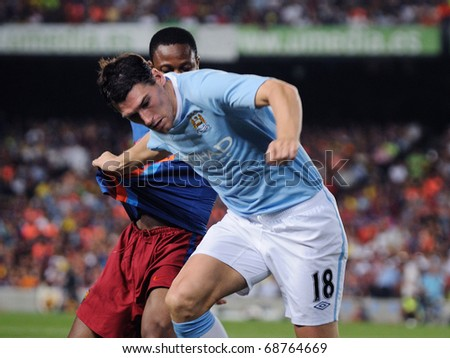 BARCELONA, SPAIN - AUG 19: Barry, Manchester City player, fights against Keita, of FC Barcelona. Joan Gamper Throphy at the Camp Nou Stadium on August 19, 2009 in Barcelona, Spain. - stock photo