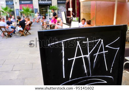BARCELONA, SPAIN - AUGUST 16: A blackboard with word tapas in a restaurant terrace in Born district on August 16, 2011 in Barcelona, Spain. This district houses a large number of bars and restaurants