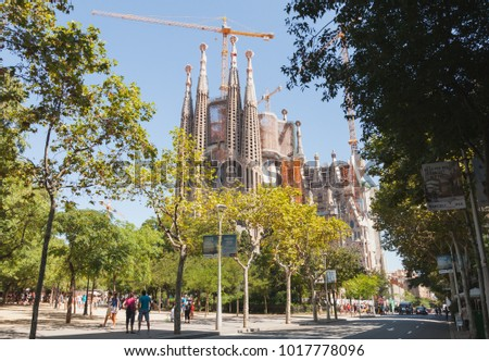 Barcelona, Spain - August 27, 2014: La Sagrada Familia, Catholic cathedral designed by Antoni Gaudi, which is being build since 1882 and still is under construction. Tourists walk on street nearby #1017778096
