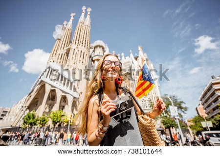 BARCELONA, SPAIN - August 16, 2017: Young woman tourist standing with catalan flag in front of the famous Sagrada Familia Roman Catholic church in Barcelona, designed by architect Antoni Gaudi #738101644