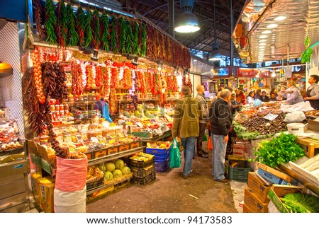 BARCELONA, SPAIN - DECEMBER 20: Tourists shop in famous La Boqueria market on December 20, 2011 in Barcelona, Spain. One of the oldest markets in Europe that still exist. Established 1217.