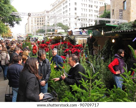 BARCELONA, SPAIN - DECEMBER 11: Unidentified people visits the famous Santa Llucia Festival to buy Christmas decoration, as pine trees and crib figures, on December 11, 2011, in Barcelona, Spain.
