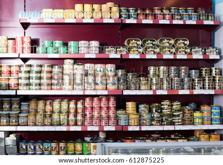 BARCELONA, SPAIN - FEBRUARY 02, 2016: Shelves with ordinary assortment of tinned and canned products in East European food store #612875225