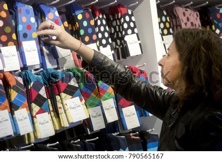 BARCELONA, SPAIN - JANUARY, 3: Shopper watching socks and prices in clothing shop on city centre on January 3, 2018 in Barcelona, Spain #790565167