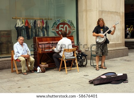 BARCELONA, SPAIN - JULY 15: male musicians playing in the street for money on July 16, 2010, in Barcelona, Spain. Spain is going through economic hardship these days.