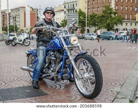 BARCELONA, SPAIN - JULY 05, 2014: Unidentified person with a Harley Davidson motorbike at an exhibition during BARCELONA HARLEY DAYS 2014, The event brought together over 12,000 motorcycles.