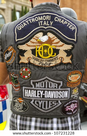 BARCELONA, SPAIN - JULY 08: Unidentified persons with typical biker jacket a Harley Davidson motorbike at an exhibition during BARCELONA HARLEY DAYS 2012, on July 08, 2012, Barcelona, Spain.