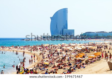 BARCELONA SPAIN JUNE 28 Barceloneta Beach against W Barcelona Hotel in summer in June 28 2013 in Barcelona Spain Barceloneta Beach one of the most popular in the city