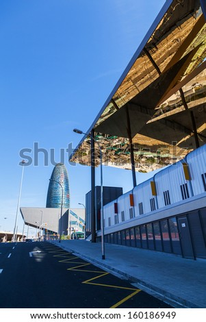 BARCELONA, SPAIN - OCTOBER 13: modern architecture on October 13, 2013 in Barcelona. view of DHUB Museu del Disseny de Barcelona and the famous Torre Agbar, above the modern ceiling of a flea market.