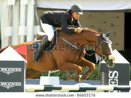 BARCELONA, SPAIN - SEPT, 23: Primitivo Nieves in action rides horse Viking Van Den Dael during the 100th CSIO event at the Real Club de Polo Barcelona on September 23, 2011 in Barcelona, Spain - stock photo