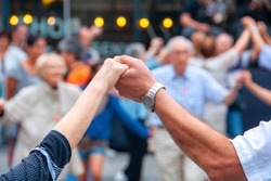 Barcelona, Spain. View of senior people holding hands and dancing national dance Sardana at Plaza Nova, Barcelona, Spain. Old hands in front of blurred people