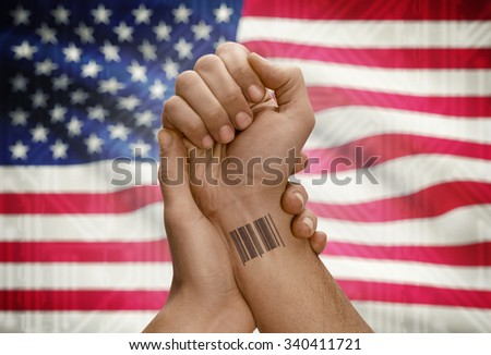 Barcode ID number tattoo on wrist of dark skinned person and national flag on background - United States