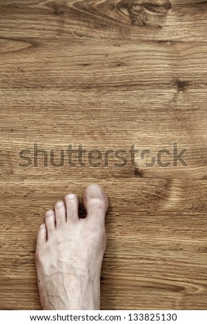 Bare and somewhat hairy left foot of an adult caucasian man, on brown parquet floor. Viewed from directly above.