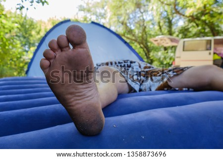 Bare dirty male feet resting on a plastic inflatable mattress outdoors #1358873696