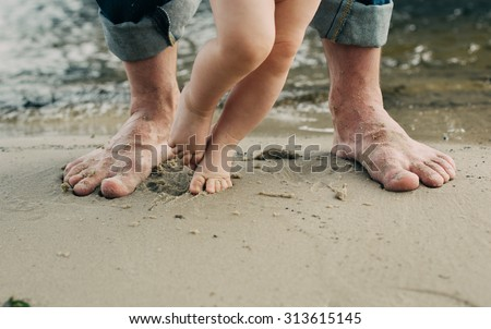 Bare feet father and his little son staying in the sand near the water  #313615145