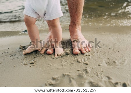 Bare feet father and his little son staying in the sand near the water  #313615259