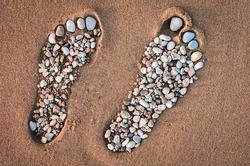Bare feet made of pebble on the sandy beach