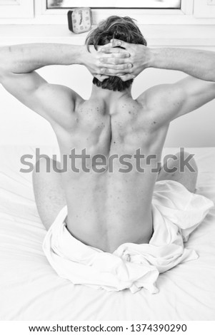 Bare feet of a man peeking out from under the cove. Picture showing young man stretching in bed. Morning bed active funny