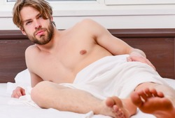 Bare feet of a man peeking out from under the cove. Stretch after wake up in the morning. Man on the bed