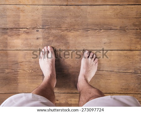Bare feet of a runner on a wooden floor background #273097724