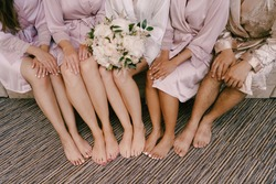 Bare feet of bridesmaids and bride with a bouquet of flowers