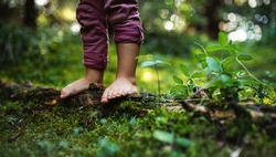 Bare feet of small child standing barefoot outdoors in nature, grounding concept.