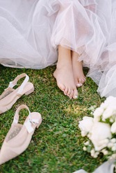 Bare feet of the bride on the grass, next to shoes and a bouquet. Wedding in Florence, Italy, in an old villa-winery.
