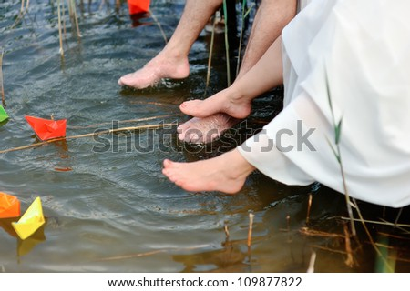 Bare feet of the newly-married couple hang down over water where paper ships float