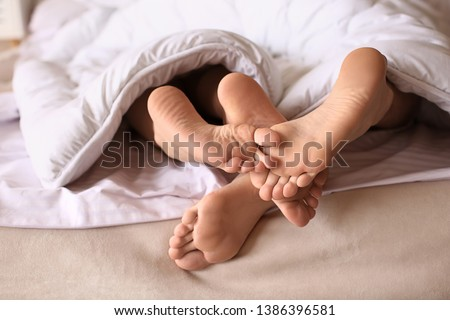Bare feet of young couple lying under blanket in bed