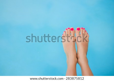 Bare feet over blue swimming pool water #283875812