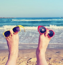Bare feet raised up with colored sunglasses on the beach. Beautiful sea surf and blue sunny sky in background. Summer vacation. Funny imagination happy character