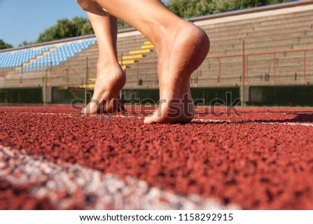Bare feet ready to depart on a red lane of the athletic ring